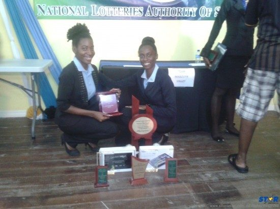 Ezbai Francis (L) and Rhyesa Joseph (R) with their winning trophy and individual prizes and awards.