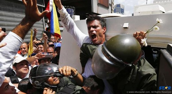 Venezuelan opposition leader Leopoldo Lopez gets into a National Guard armored vehicle in Caracas February 18, 2014.