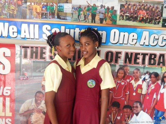Jana James (l) and Shirlianna Lamontagne (r) pose proudly before SCSS collage of recent successes, as the latest Soufriere students to do their school proud.