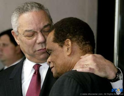 Julian Hunte (r) being embraced by Colin Powell former US Secretary of State.
