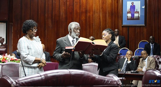 Former Permanent Secretary of the Public Service Ministry, Mark Louis, now a vision commissioner, takes the oath of office on Monday.  On the left, a solemn Dame Pearlette Louisy looks on.