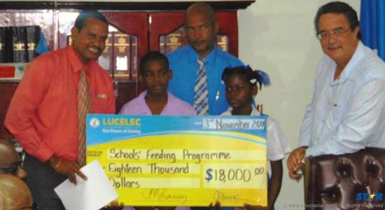 LUCELEC Corporate Communications Manager Roger Joseph (left) presenting  the LUCELEC Trust $18,000 contribution to the revamped School Feeding Programme to representatives of the Vieux Fort Primary School and Prime Minister Dr. Kenny Anthony.