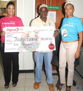$10,000 Christmas winner Julian Eugene with Digicel's Sergin John Baptiste and Natasha Meda.