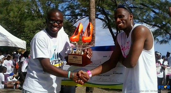 Julian Touissant (right) receives his trophy from     Richard Percell General Manager of the CCCL, group parent company of the WAVE 94.5 - organizers of the event.