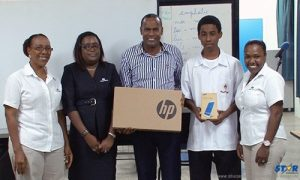 Principal of St. Mary's college Rohan Seon stands proudly with student, teacher and Caribbean metals representatives.