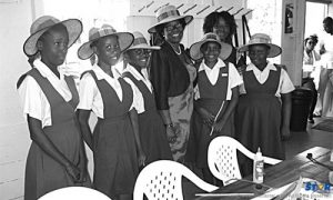 Members of Grow Well's Girls' Circle model hats they designed for the Governor General.  Members of Grow Well's Remedial Reading Programme, its library, and its computer lab were in awe but soon lost their shyness as Dame Pearlette encouraged them to read to her and share information about their computer projects.