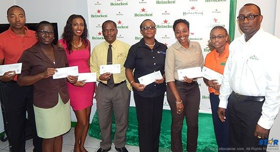 Saint Lucia Tourist Board Public Relations Manager (left) and Heineken Brand Manager Gaius Harry (extreme right) pose with Heineken sponsorship recipients Wednesday.