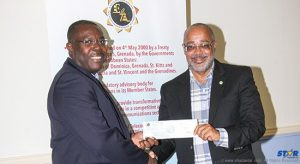 Chairman of ECTEL's Board of Directors, Mr. Isaac Solomon, hands over a cheque to Director General of the OECS Commission, Dr. Didacus Jules.