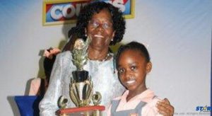 Arianna Mercier of Camille Henry Memorial School receives her winner's trophy from Dame Pearlette Louisy.