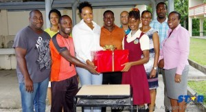 A current student of the Soufriere Comprehensive Secondary School accepts on behalf of her peers a donation from past students of the school.