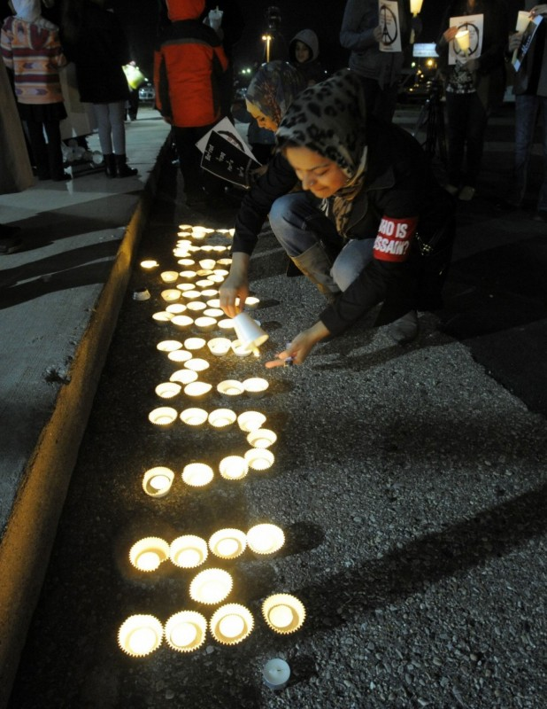 Sara Syeda lights one of a group of candles spelling the word humanity on Nov. 14 during a candlelight vigil in support of the victims of the Paris attacks and Beirut bombings at the Islamic Center of America in Dearborn. Mich. (Steve Perez/Detroit News via AP)