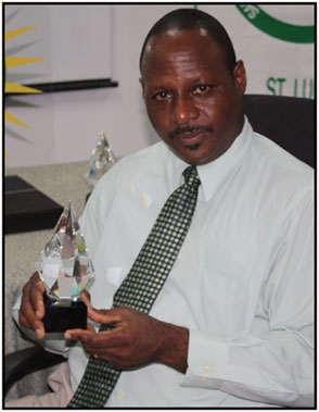 Executive Director of the Saint Lucia Chamber of Commerce, Industry and Agriculture Brian Louisy with one of the prestigious trophies up for grabs at this year's Chamber Awards.
