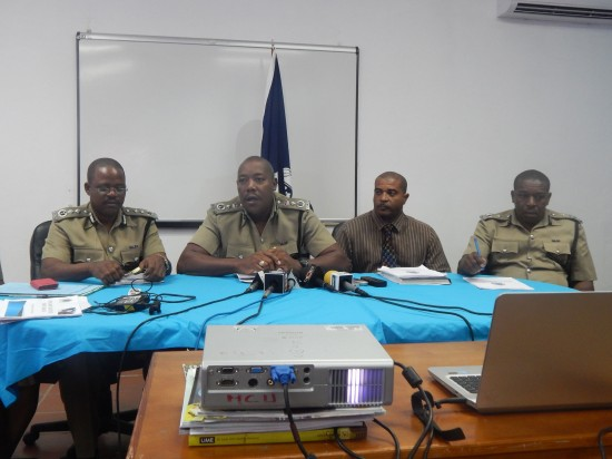 Errol Alexander (centre), in his role as acting police commissioner, addresses, with leading members of the force, questions from local media personnel. The unanswered question remains: How much of what he says is worth the paper it's scripted on?