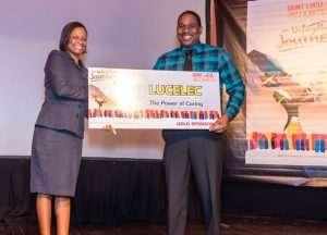 LUCELEC Corporate Communications Assistant Bernardia Regis presenting Tourist Board Director Louis Lewis with the company's commitment to the 2016 Saint Lucia Jazz and Arts Festival.